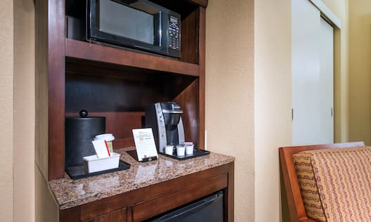 Hospitality Center With Microwave, Keurig, and Mini Fridge by Armchair in Suite