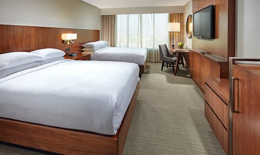 Two Queen Beds with Work Desk and Wall-Mounted TV