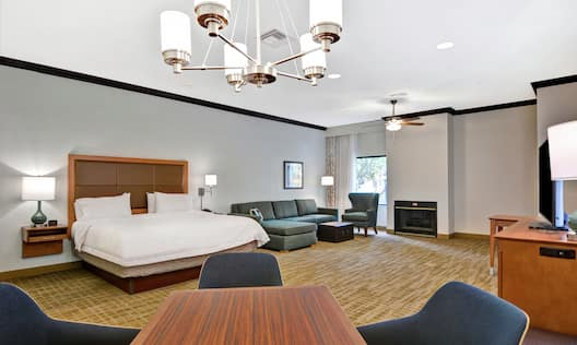 Guestroom with King Bed, Couch, Lounge Chair, Fireplace, Dining Table and Television