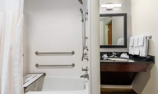 Accessible Bathtub With Grab Bars, Seat, and Handheld Showerhead, Vanity Mirror, Sink, Towels, and Toiletries