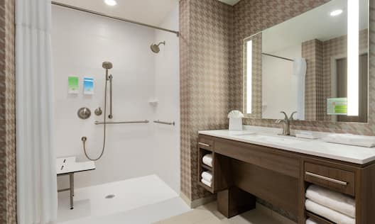 Spacious accessible bathroom featuring roll in shower with seat. mobile shower head, vanity, and mirror.