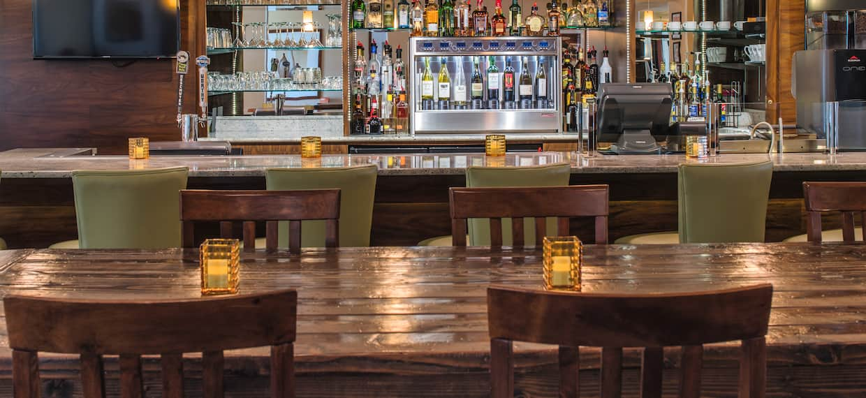 Fully Stocked Bar With Counter Seating, TV, Tables With Candles, and Chairs