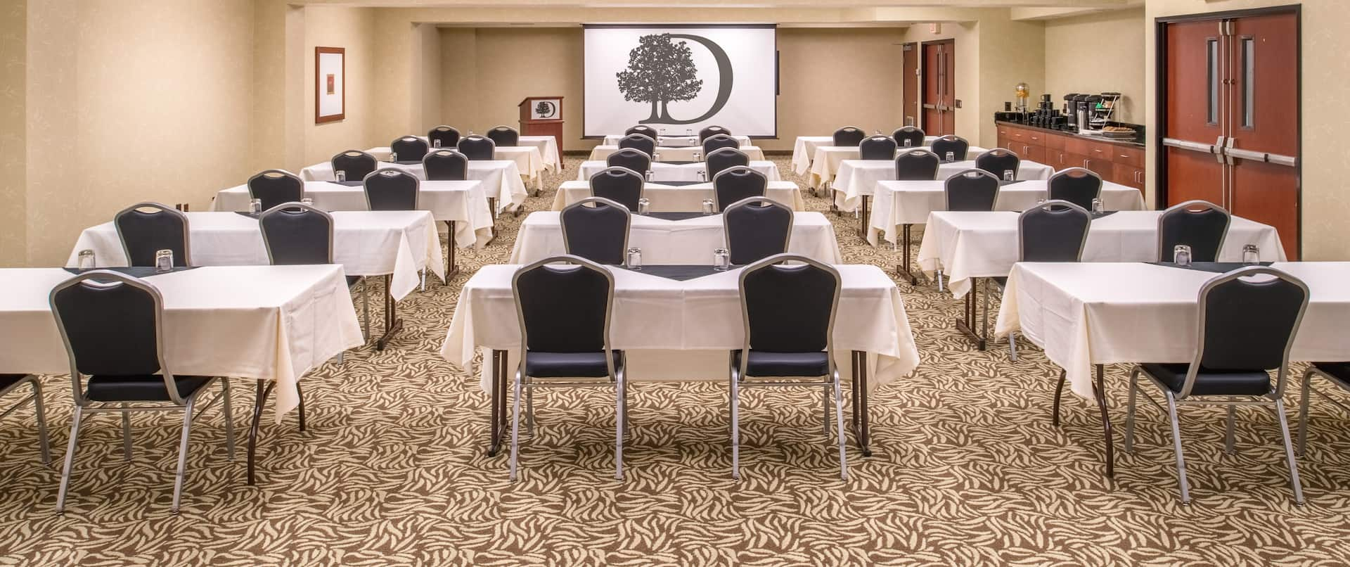 Classroom Setup in Large Meeting Room With Wall Art, Refreshment Counter, Two Entry Doors, Tables, Chairs, Podium, and Presentation Screen