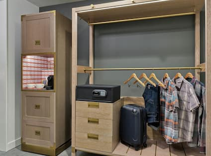 Close Up of Nespresso Coffee Bar, Room Safe, and Clothes Hanging in Open Closet in Accessible Guest Room