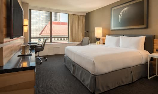 King bed with soft chair, work desk, TV, and window with city view