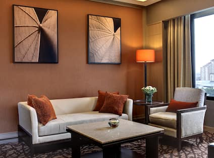 King Deluxe Suite Living Area with Lounge Sofa and Chair, Art on the Wall, and Window with Outdoor View
