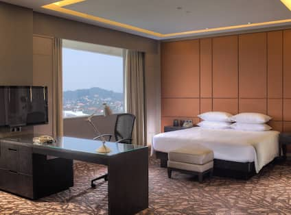 King Royal Suite Bedroom with King Bed, Footrest, Work Desk, TV and Window with Outdoor View