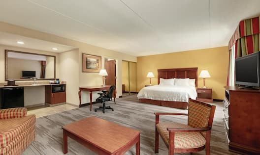 1 King studio mobility accessible room featuring bed, sitting area, TV, desk and wet bar.
