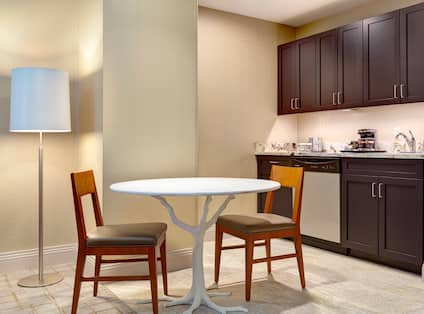 Illuminated Floor Lamp, Seating for Two at White Dining Table, and Kitchenette With Dark Wood Cabinets, Coffee Maker, Sink and Dishwasher