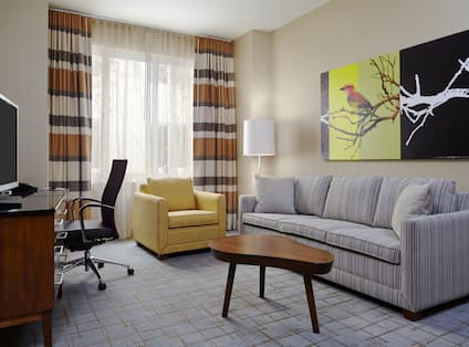TV, Work Desk, Window WIth Long Drapes, Armchair, Floor Lamp, Wall Art Above Sofa, and Coffee Table in Suite Seating Area