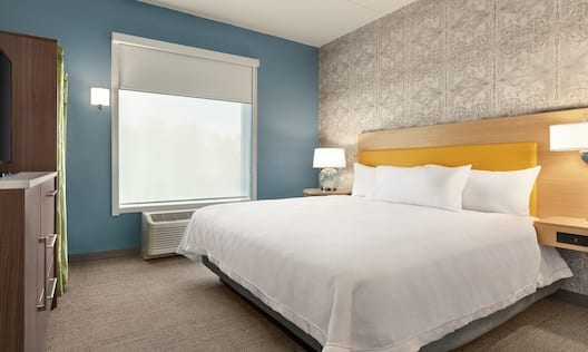 Bright private bedroom in suite featuring comfortable king bed, TV, and air conditioning unit by window.