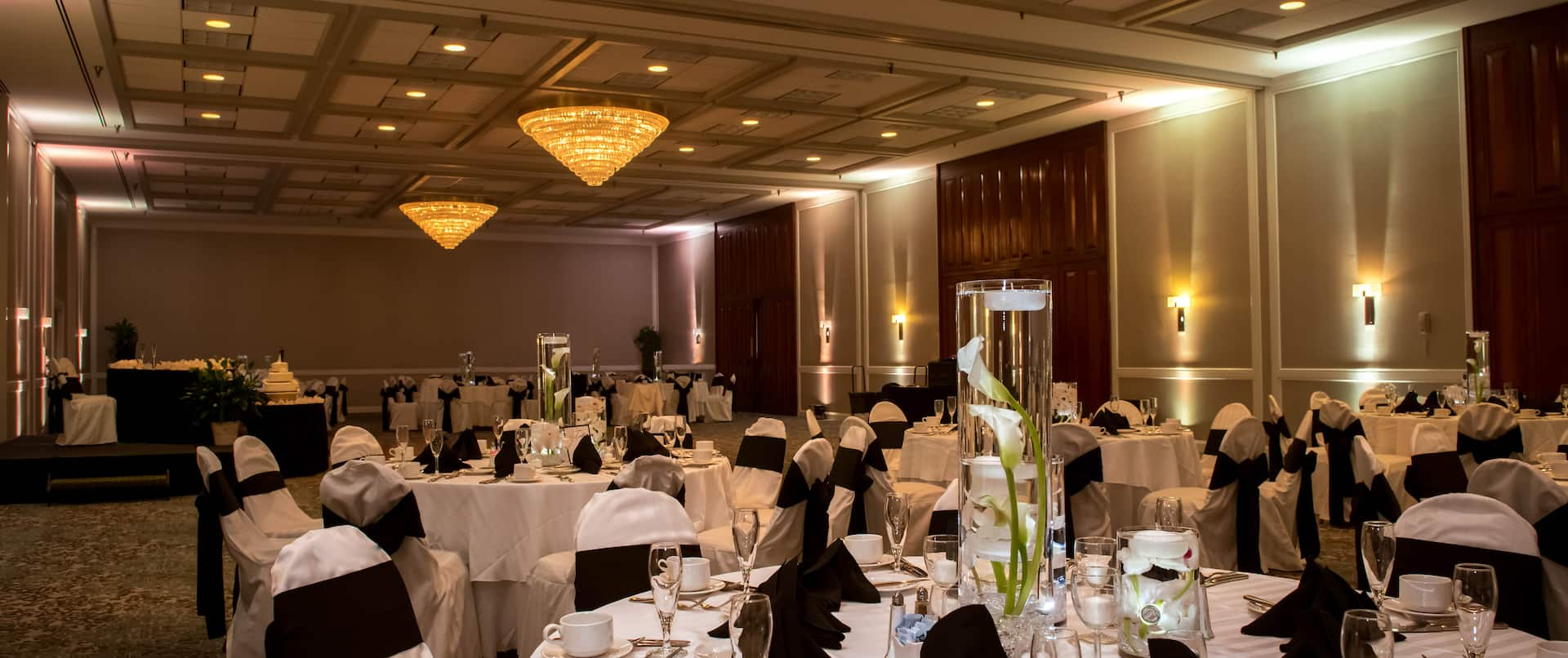 Flowers in Water With Floating Candles, Place Settings, and Black Napkins on Tables With White Linens, and White Chairs With Black Bows in Ballroom Set Up for Wedding