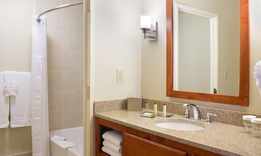 Fresh Towels by Tub, Vanity Mirror, Sink, Granite Countertop, Amenities, and Toiletries in Guest Bathroom