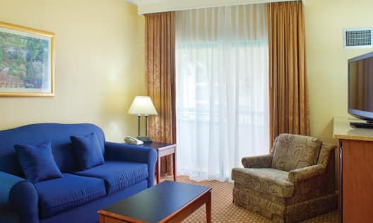 Wall Art Above Blue Sofa, Coffee Table, Illuminated Table on Side Tables, Window With Long Drapes, Armchairs, and TV in Atrium Suite Living Area