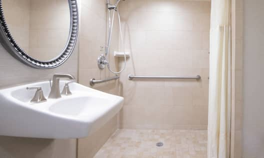 Available upon request, our accessible bathrooms offer a roll-in shower and pull-out bench.
