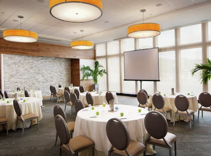 Meeting Room Set up with Round Tables and a Projection Screen