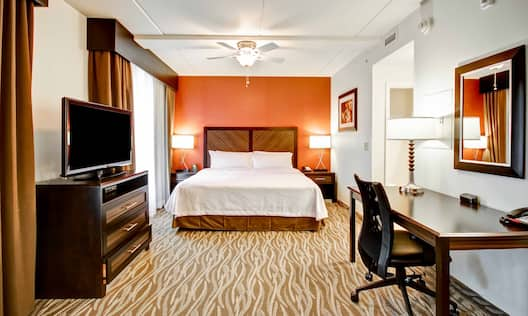Suite with bed, work desk, and TV