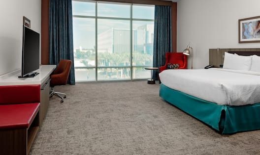 Guest Room with City View and Large Bed Armchair Desk and HDTV