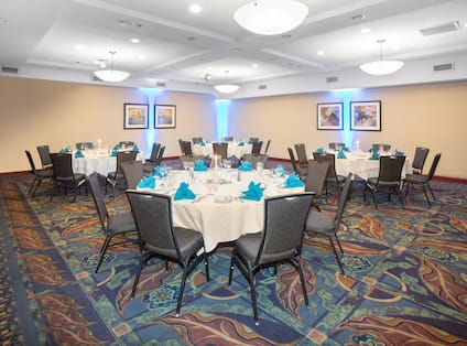 Social Dinner in Meeting Room with Four Large Round Tables with Eight Place settings and Blue Napkins