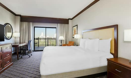 Guest room with a king sized bed desk balcony and HDTV