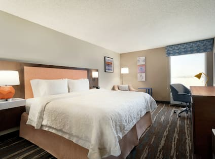 Guestroom with King Bed Lounge Chair Work Desk and Television