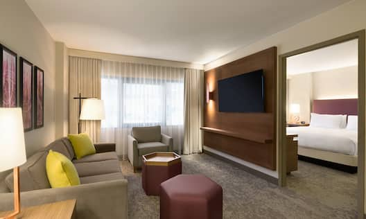 Guest Suite Living Room with Sofa, Armchair, Footrests, Wall Mounted HDTV and Bedroom Entry