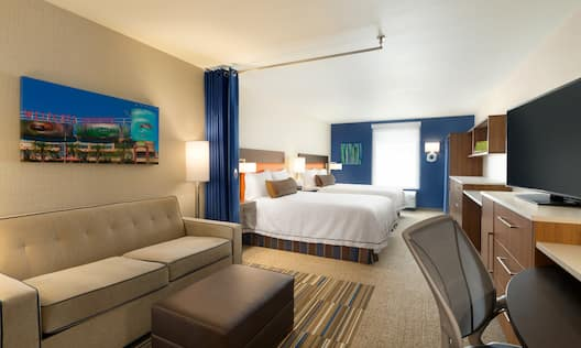 Wall Art Above Sofa, Ottoman, and Illuminated Floor Lamp Facing Work Desk and TV, Blue Partition Curtain Open With View of Two Queen Beds, Lamps on Bedside Tables and  Window in Studio Suite