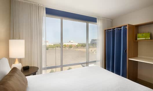 Neatly Made Bed, Illuminated Lamp on Bedside Table by Large Window With Stadium View, Closet With Blue Blue Drapes and Wood Shelves