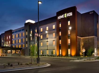 Angled View of Illuminated Parking Lot, Hotel Exterior With Signage, Entrance, Landscaping, and Flagpole at Night