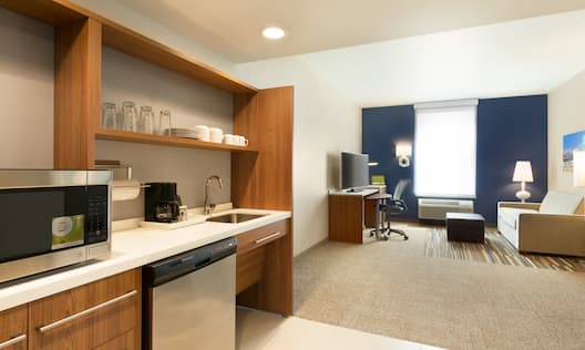 Accessible Studio Kitchen With Microwave on Counter, Dishes on Wood Cabinets, Dishwasher, and Sink, Living Room With TV, Work Desk, Illuminated Lamps, Wall Art Above Sofa, and Ottoman