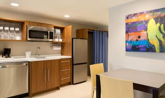 Suite Kitchen Featuring Artwork Over Dining Table, Wood Cabinets, Dishwasher, Microwave and Fridge