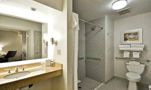 A Guest Bathtub with Bench and Grab Bars