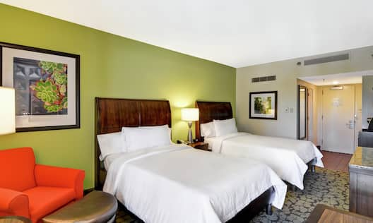 Guest Room with Two Double Beds, Orange Chair and Semi Circle Ottoman