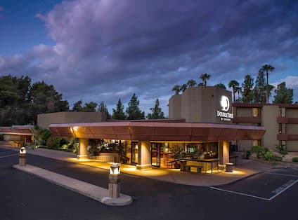 Hotel Exterior, Signage, Entrance, Landscaping, and Parking Lot Illuminated at Night