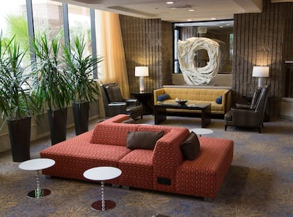 Art Feature Surrounded by Soft Seating, Tables, Illuminated Lamps, Plants and Large Windows With Open Drapes in Lobby