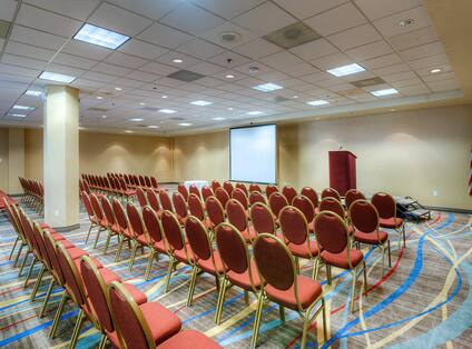 Meeting Room Arranged Theater Style With Rows of Chairs Facing Projector Screen, Flag, and Stage with Podium