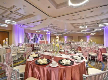 A large ballroom with tables, chairs and table settings