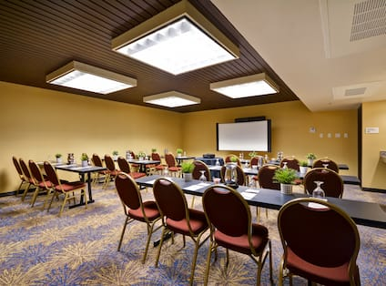 A meeting room with long tables and chairs
