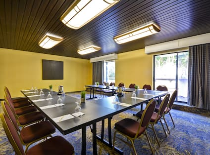 A meeting room with u shaped table and chairs