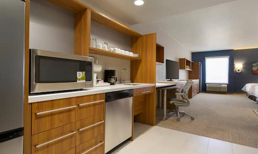 Accessible Studio Suite With Microwave on Counter, Dishes in Wood Cabinets, Coffee Maker, and Dishwasher in  Kitchen, Work Desk, TV, Window and Two Queen Beds