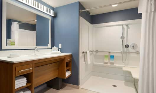 Large Vanity Mirror, Sink, Fresh Towels, Toiletries, and Roll-In Shower With Grab Bars