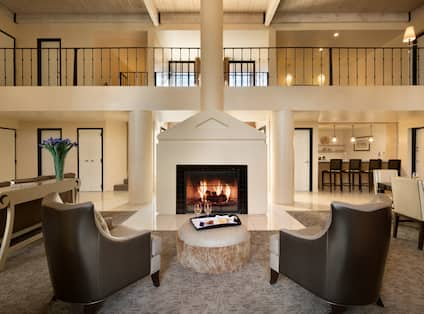 Presidential Suite Living Room With Soft Seating and Table Around Fireplace, Dining Table, Counter Seating at Kitchen Bar, and View of Second Floor Railing