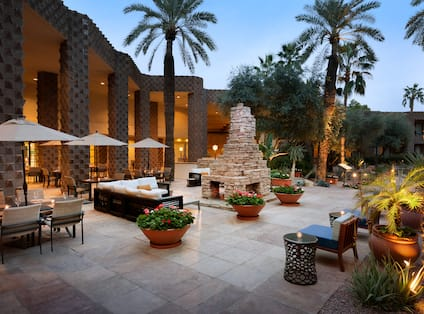 Tables With Umbrellas, Soft Seating, Furnace, and Candlelit Tables on Outdoor Patio Surrounded by Palm Trees at Dusk