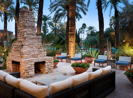 Illuminated Outdoor Patio With Furnace, Candlelit Tables, and Mixed Seating Surrounded by Palm Trees at Dusk