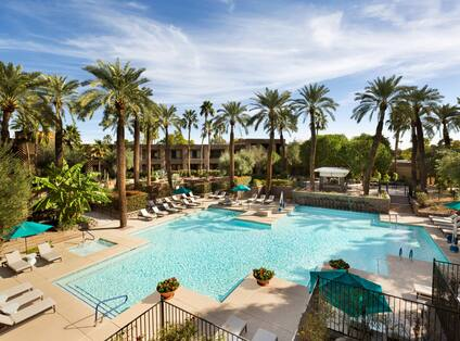 Daytime View of Green Sun Umbrellas, and Loungers by North Outdoor Pool Surrounded by Palm Trees and Hotel Exterior in Background