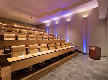 Classroom Setup in Chambers Room With Stadium Seating, Desks, Podium, and Presentation Screen