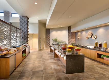 Asadero Cocina & Cantina Buffet Area With Hot and Cold Selections, Plates, Utensils, Condiments, Beverage Containers, Drinking Glasses and Wall Art