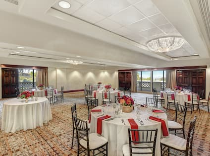 White linens with red napkins on round tables in reception space