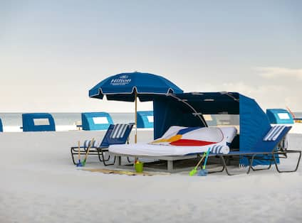 Beach umbrella and cabana with two lounge chairs, ocean in background