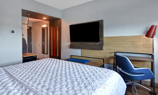 guest room with bed television and work desk